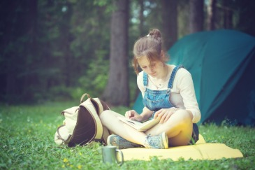 girl hiker sitting and reading a book near the tent