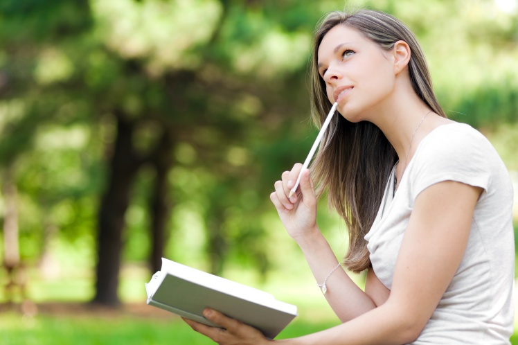 Girl at the park writes in her personal diary